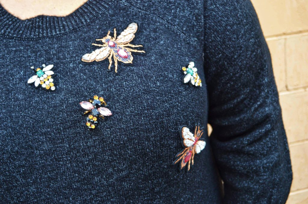 Sweater with bugs applique on it
