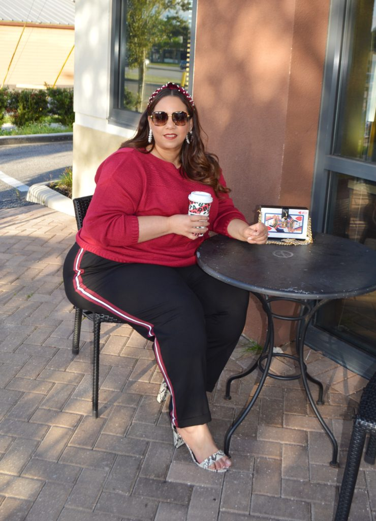 Plus size fashion blogger Farrah Estrella wearing a sweater and a side stripe trouser